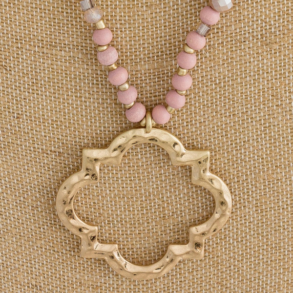 """Long wood beaded necklace featuring a clover lotus inspired pendant and iridescent bead accents. Pendant approximately 2"""". Approximately 34"""" in length."""