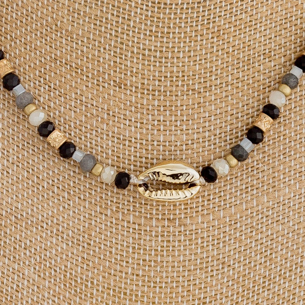 "Iridescent beaded choker featuring a puka shell detail and gold metal accent. Approximately 14"" in length."