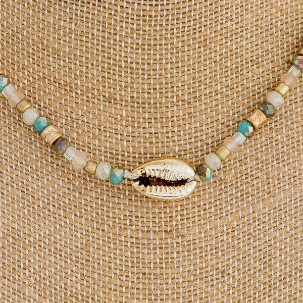 """Iridescent beaded choker featuring a puka shell detail and gold metal accent. Approximately 14"""" in length."""