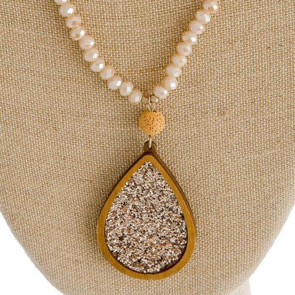 """Beaded necklace featuring a wooden glitter teardrop pendant with lava rock accent. Pendant approximately 3"""". Approximately 36"""" in length overall."""