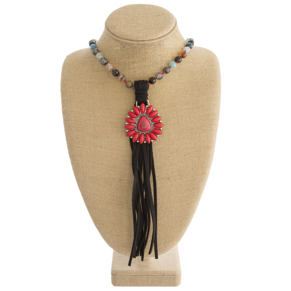"Long beaded western style necklace featuring a natural stone pendant with faux leather tassel details. Pendant approximately 10"". Approximately 50"" in length overall."