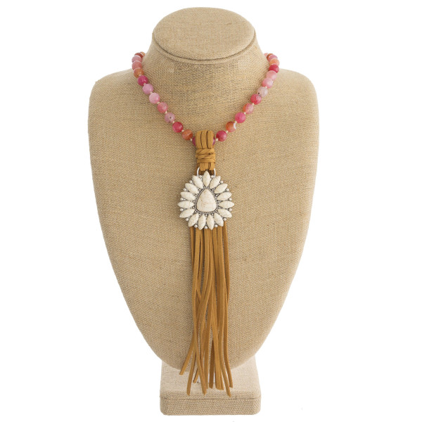 """Long beaded western style necklace featuring a natural stone pendant with faux leather tassel details. Pendant approximately 10"""". Approximately 50"""" in length overall."""