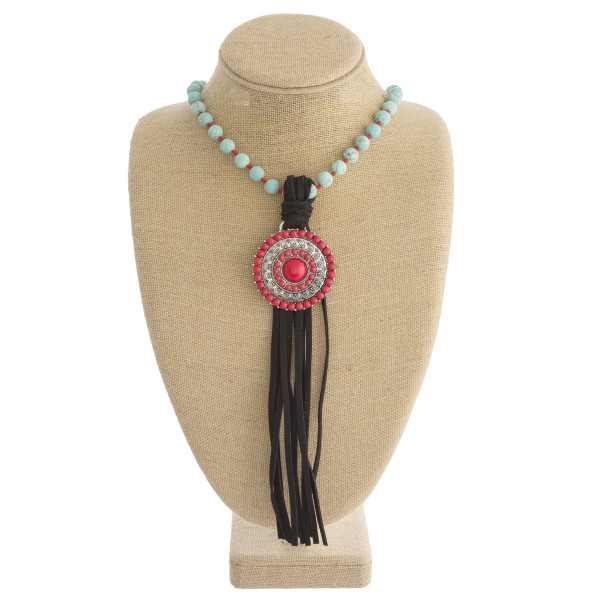 "Long natural stone beaded necklace featuring a western style pendant with faux leather tassel details. Pendant approximately 10"". Approximately 50"" in length overall."
