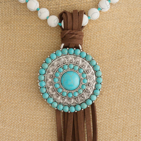 """Long natural stone beaded necklace featuring a western style pendant with faux leather tassel details. Pendant approximately 10"""". Approximately 50"""" in length overall."""
