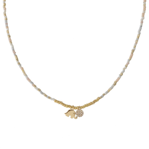 """Dainty seed beaded necklace featuring an elephant and disc accent with cubic zirconia details. Approximately 16"""" in length."""
