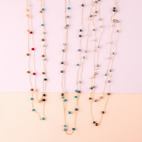 "Long dainty beaded layered chain necklace featuring faceted bead details. Approximately 32"" in length."