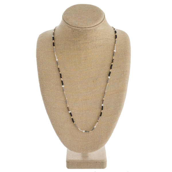 """Long dainty beaded necklace featuring wood, iridescent and faceted bead details with pearl and gold accents. Approximately 32"""" in length."""