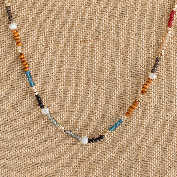 "Long dainty beaded necklace featuring wood, iridescent and faceted bead details with pearl and gold accents. Approximately 32"" in length."