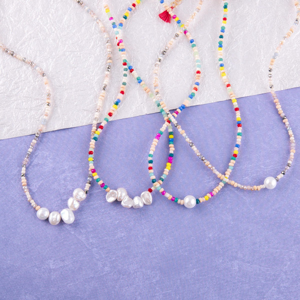 "Beaded necklace featuring seed, iridescent and wood bead details with pearl accents. Approximately 16"" in length."