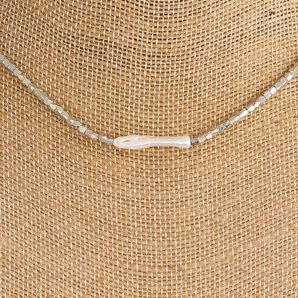 "Faceted beaded necklace featuring a faux pearl accent. Approximately 15"" in length"