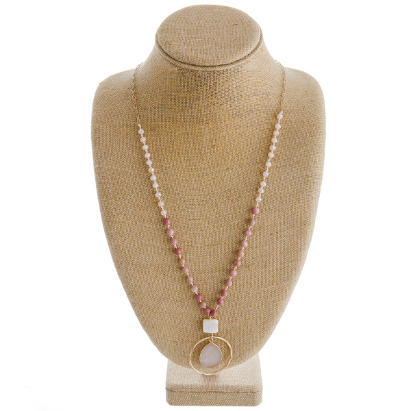 "Long oval link/faceted beaded necklace featuring a round pendant with natural stone an resin accents. Pendant approximately 2.5"". Approximately 36"" in length overall."