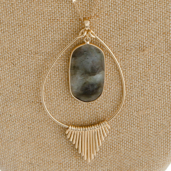 "Long metal chain necklace featuring a teardrop pendant with a natural stone center detail and gold tassel accents. Pendant approximately 4"". Approximately 34"" in length overall."