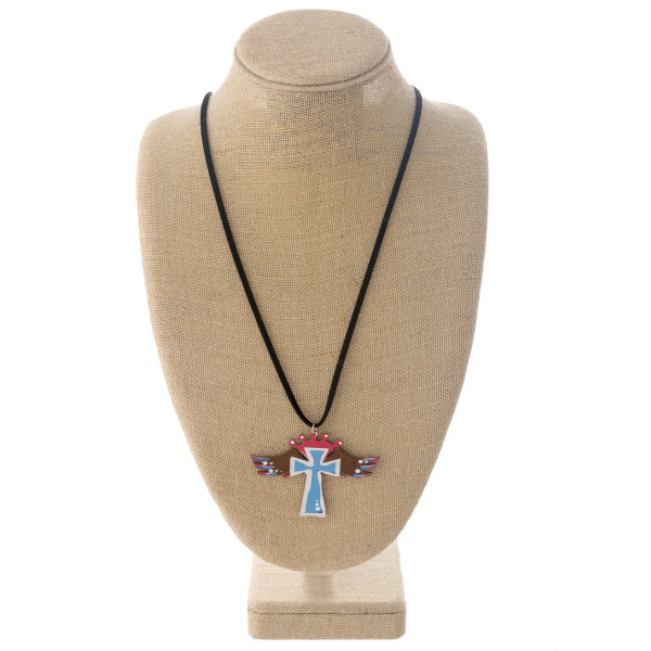 """Long black felt necklace featuring a cross metal pendant with wings and crown details. Pendant approximately 2.5"""". Approximately 36"""" in length overall."""