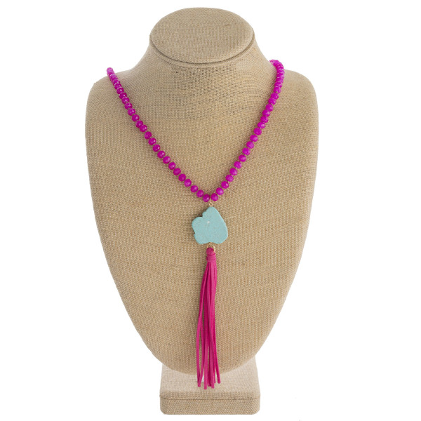 """Long faceted beaded necklace featuring faux leather tassel details with a turquoise natural stone accent. Approximately 42"""" in length."""
