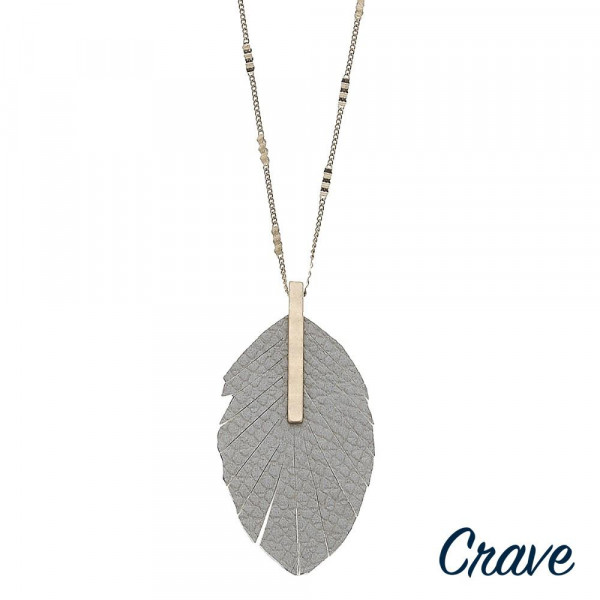 """Gold chain necklace featuring a faux leather feather pendant with snakeskin details and a gold metal bar accent. Pendant approximately 3.5"""". Approximately 36"""" in length overall."""