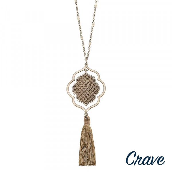 "Long gold chain necklace featuring a lotus pendant with faux leather snakeskin details and a tassel accent. Pendant approximately 4.5"". Approximately 36"" in length overall."