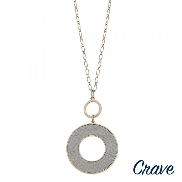 """Long gold chain necklace featuring a disc pendant with faux leather snakeskin details. Pendant approximately 2.5"""". Approximately 34"""" in length overall."""
