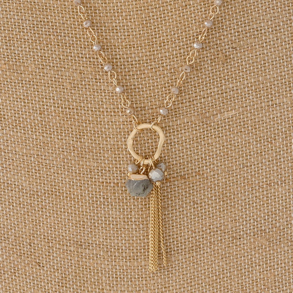 "Dainty curb chain necklace featuring faceted bead details and a charm pendant with a chain inspired tassel and faceted bead accents. Pendant approximately 2"". Approximately 20"" in length overall."