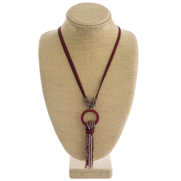 """Faux leather necklace featuring a faceted beaded tassel detail with a resin accent. Pendant approximately 6"""". Approximately 38"""" in length overall."""