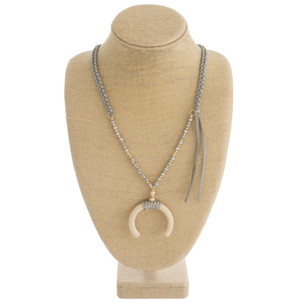 """Faux leather braided necklace with crescent pendant and beaded details. Pendant approximately 2"""" in diameter. Approximately 34"""" in length overall."""