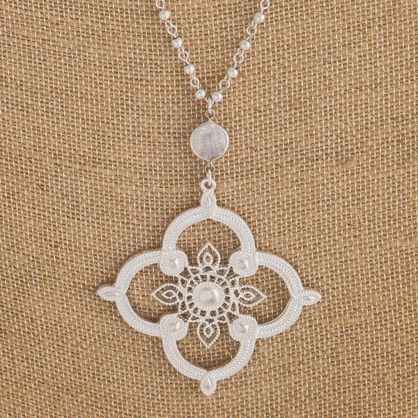 "Long cable/ball chain necklace featuring a metal flower inspired pendant with an iridescent accent. Pendant approximately 3"". Approximately 36"" in length overall."