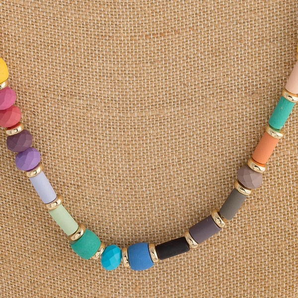 """Long color block necklace with wood and faceted bead details. Approximately 32"""" in length."""