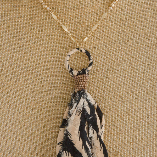 """Long animal print fabric tassel pendant necklace with beaded accents. Pendant approximately 7"""" in length. Approximately 44"""" in length overall."""