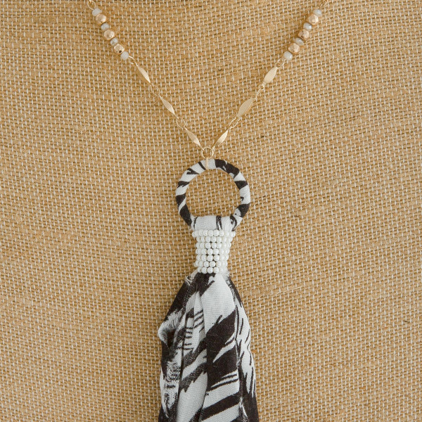"Long animal print fabric tassel pendant necklace with beaded accents. Pendant approximately 7"" in length. Approximately 44"" in length overall."