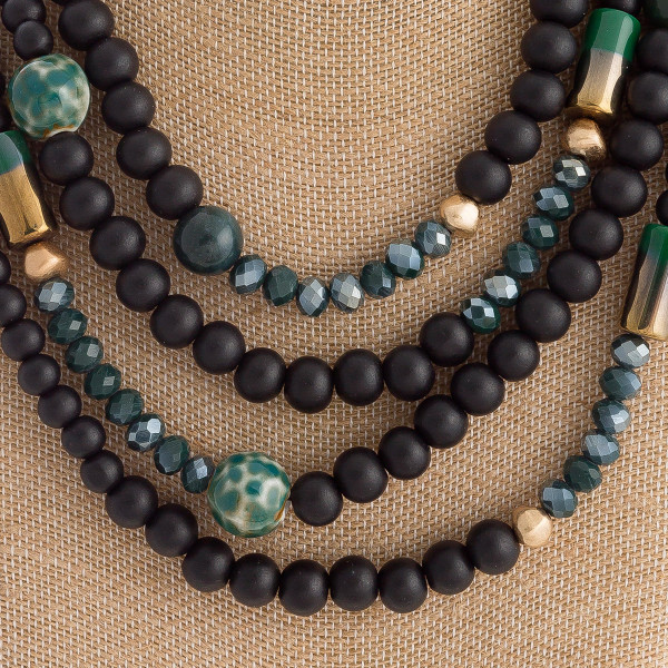 "Wood beaded layered statement necklace with glass bead details. Approximately 18"" in length."