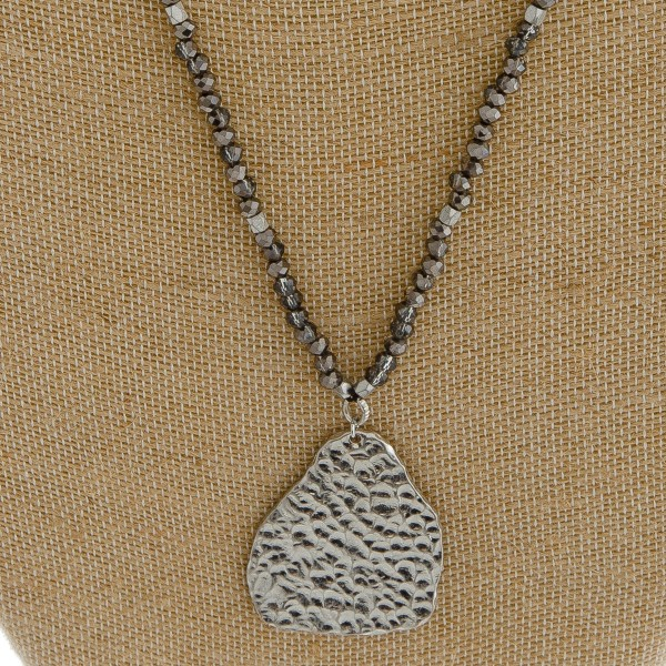 "Long beaded necklace with hammered nugget pendant.   - Pendant approximately 2"" in length  - Approximately 28"" in length overall"