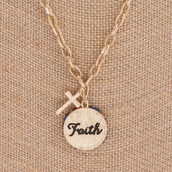 "Faith engraved disc pendant necklace featuring multicolor rhinestone accents. Pendant approximately .75"" in diameter. Approximately 20"" in length overall."