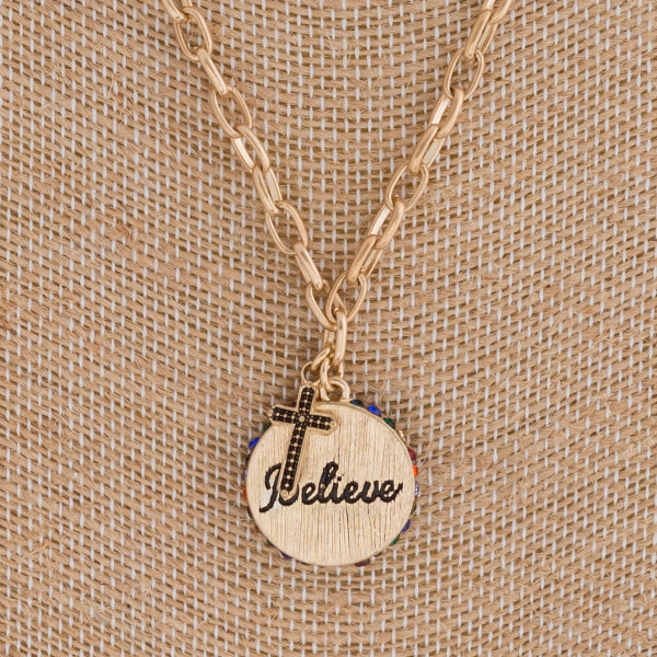 "Believe engraved disc pendant necklace featuring multicolor rhinestone accents. Pendant approximately .75"" in diameter. Approximately 20"" in length overall."