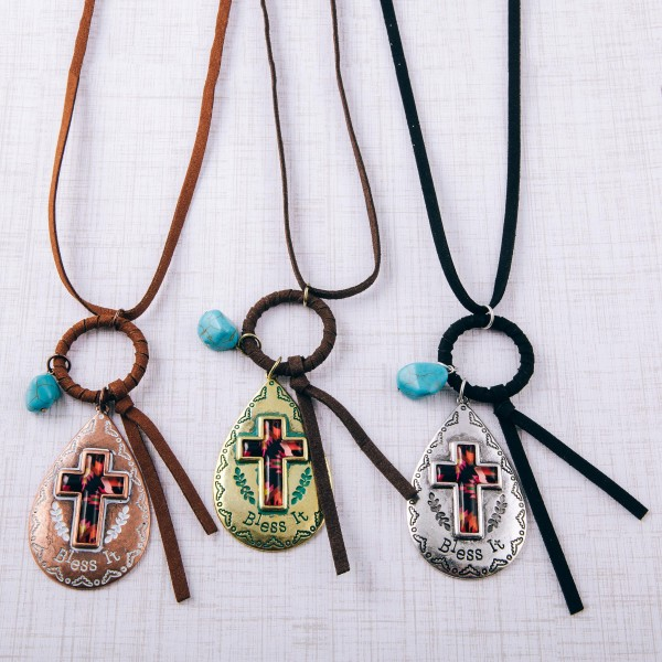 """Brown faux leather necklace featuring a patina tone teardrop cross pendant with """"Bless It"""" engraved details and natural stone accent.  - Pendant approximately 3"""" in length - Approximately 38"""" in length overall with 3.5"""" extender"""