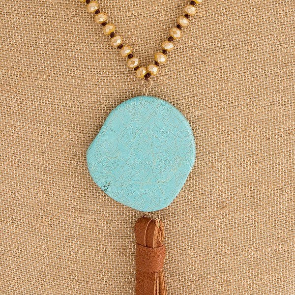 "Long cord beaded statement necklace featuring a natural stone faux leather tassel pendant. Pendant approximately 7.5"" in length. Approximately 46"" in length overall."