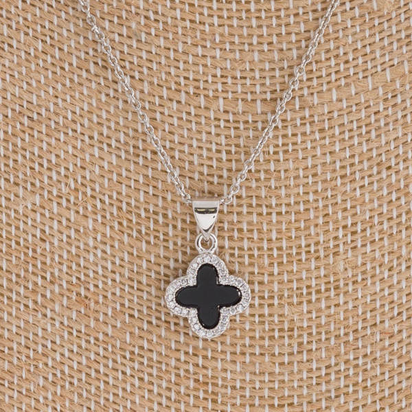"Dainty resin clover pendant featuring cubic zirconia details. Pendant 1cm in diameter. Approximately 16"" in length overall."