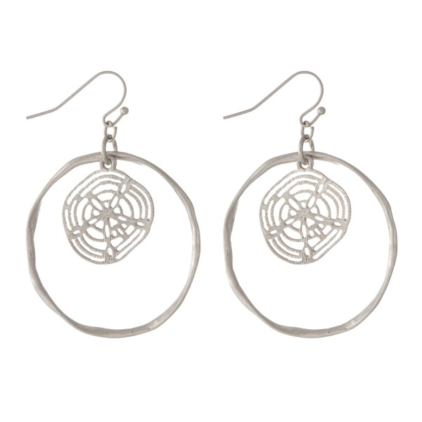 "Silver tone fishhook earrings with a hammered circle and a sand dollar. Approximately 1.25"" in diameter."