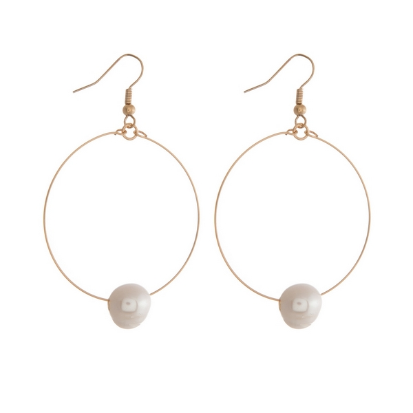 "Gold tone fishhook earrings featuring an open circle and a freshwater pearl bead. Approximately 2"" in length."