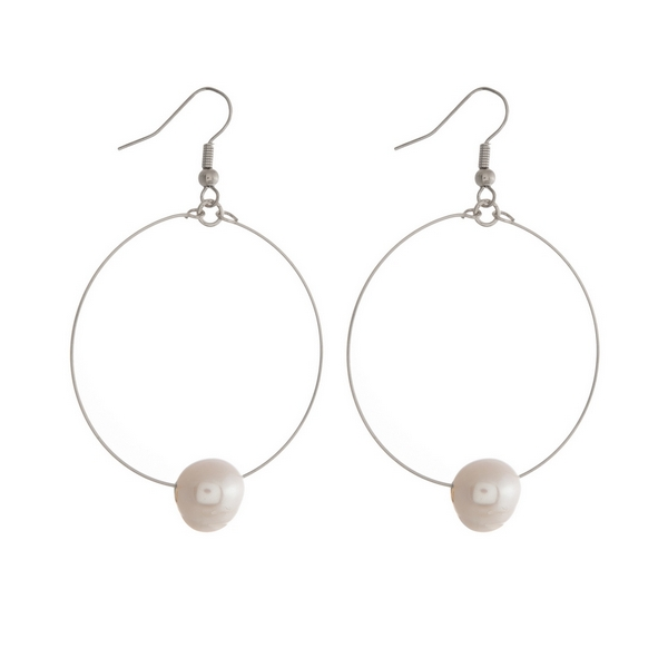 "Silver tone fishhook earrings featuring an open circle and a freshwater pearl bead. Approximately 2"" in length."