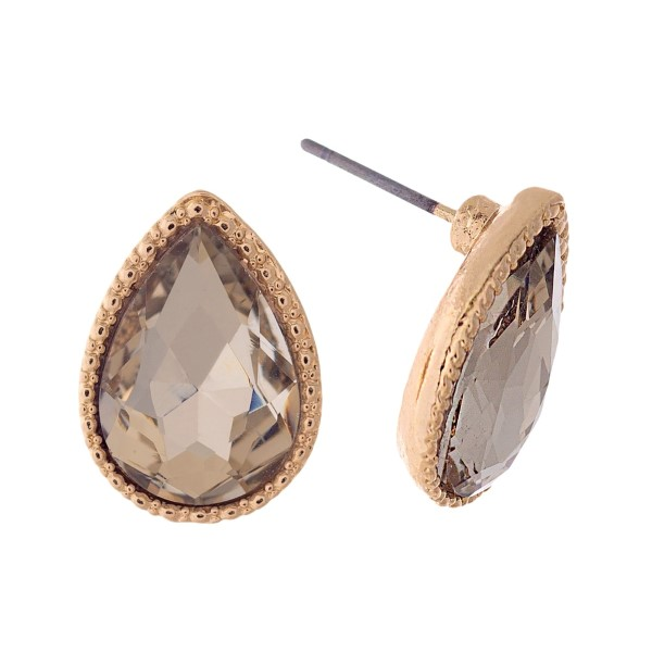 "Gold tone teardrop stud earrings with a topaz rhinestone. Approximately 1/2"" in length."