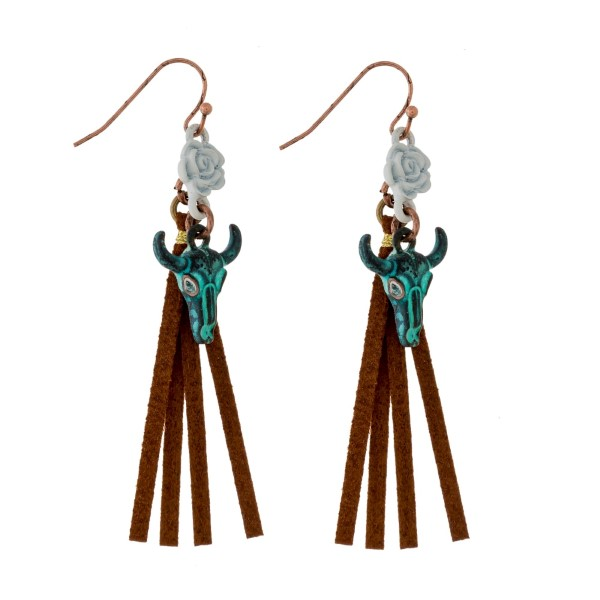 """Burnished fishhook earrings with a cow skull and faux suede tassel. Approximately 2.75"""" in length."""