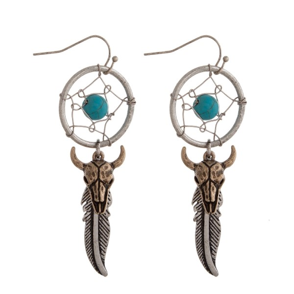 """Silver tone fishhook earrings with a dreamcatcher, feather and steer head skull. Approximately 3"""" in length."""