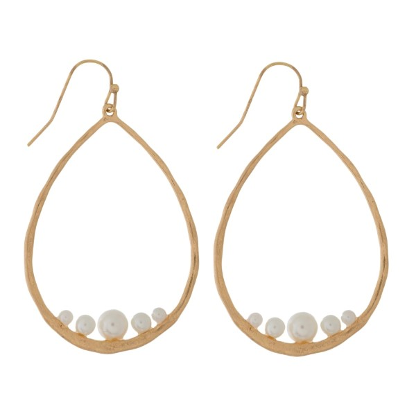 "Fishhook earrings with a hammered teardrop shape and a pearl bead. Approximately 2.5"" in length."