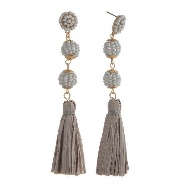 """Statement, post style earring with glass beads and raffia tassel detail. Approximately 4"""" in length."""