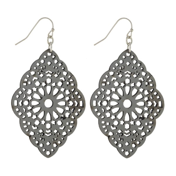 Silver tone fishhook earring with filagree cut out leather design.