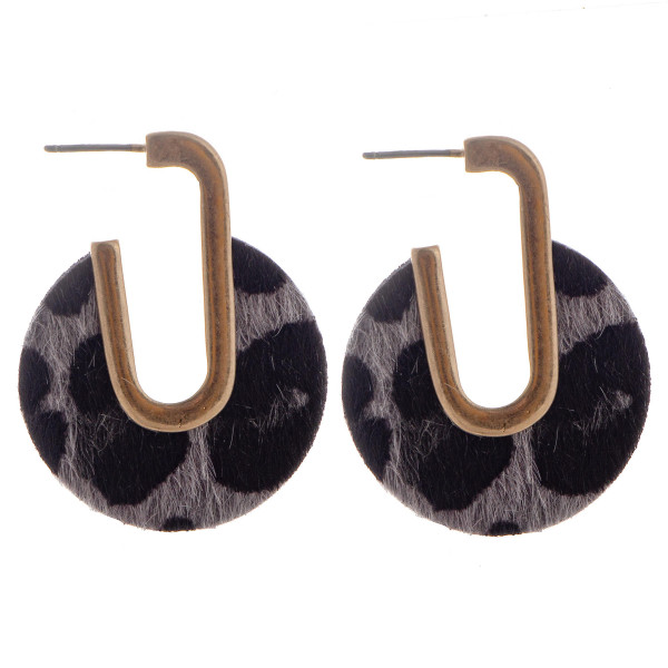 Gold tone faux leathered earrings with circular shaped animal print details. Approximate 1.5 in length.