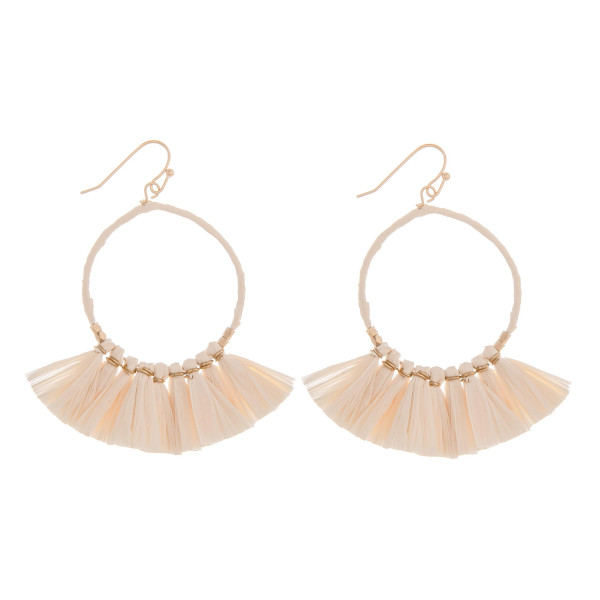 """Round metal earrings with raffia tassel details. Approximately 2"""" in length."""