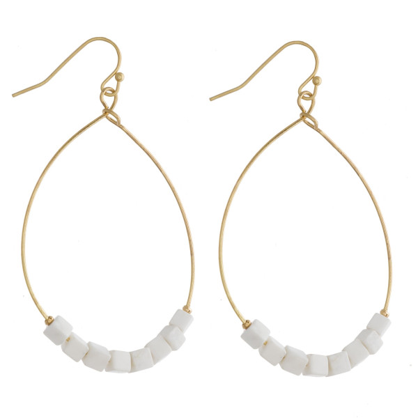 """Metal teardrop earrings featuring white natural stone beaded details. Approximately 2"""" in length."""