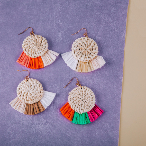 "Rattan drop earrings featuring raffia tassel details. Approximately 2"" in length."