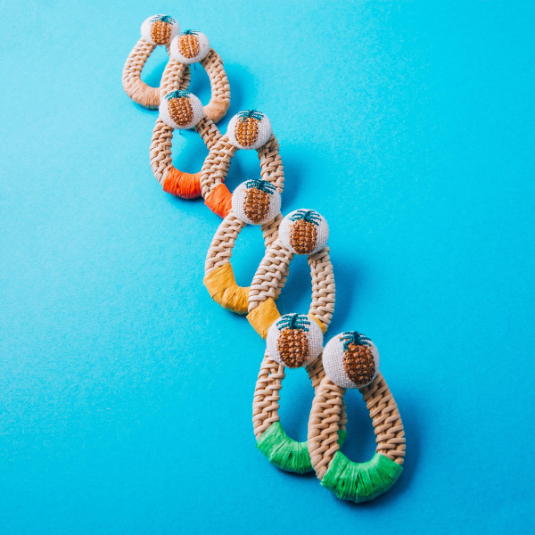 "Woven rattan teardrop earrings featuring a pineapple stud detail. Measure approximately 1.5"" in length."
