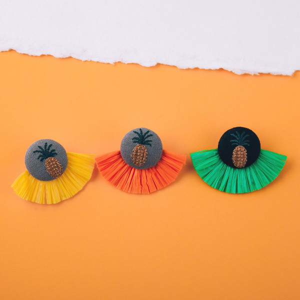 """Orange raffia tassel earrings featuring a pineapple embroidered detail with a stud post. Approximately 1.5"""" in length."""